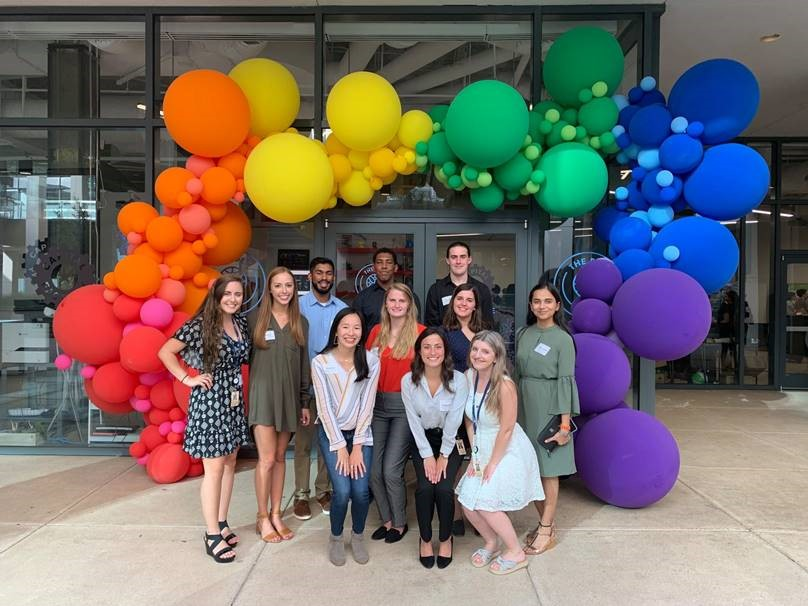 A group of 11 people pose outdoors for a picture in front of a building with a rainbow balloon arch.