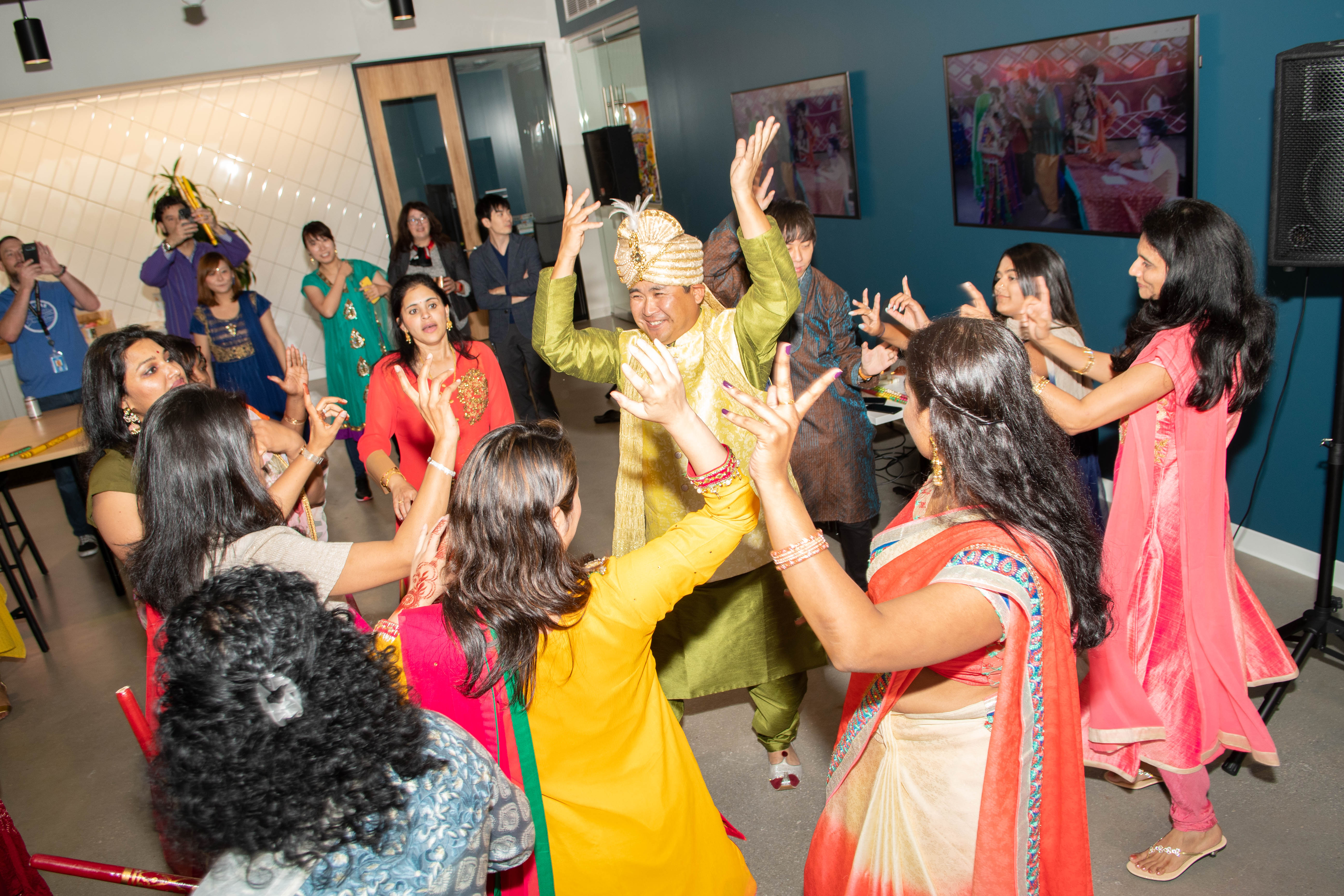A group of people dancing indoors. They wear colorful clothing. This is part of a Diwali celebration.