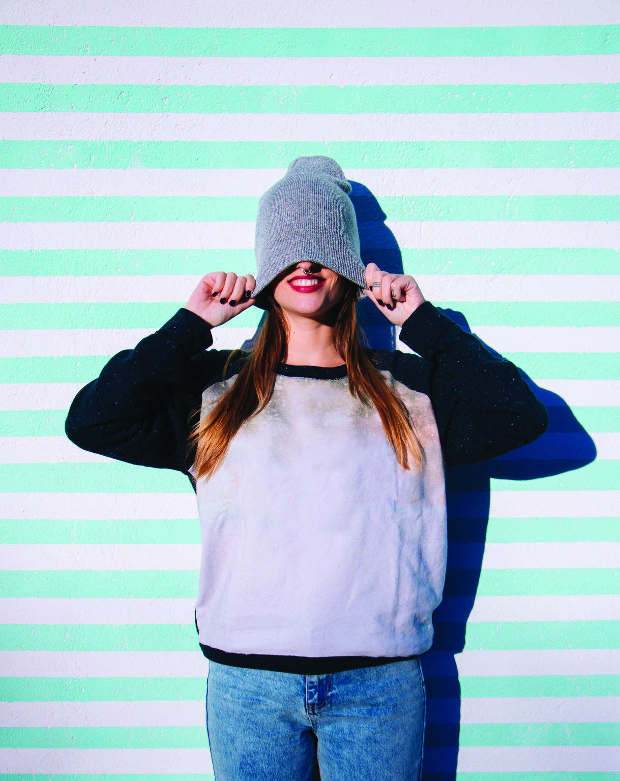 A girl against a striped wall pulls her beanie over her head and smiles.