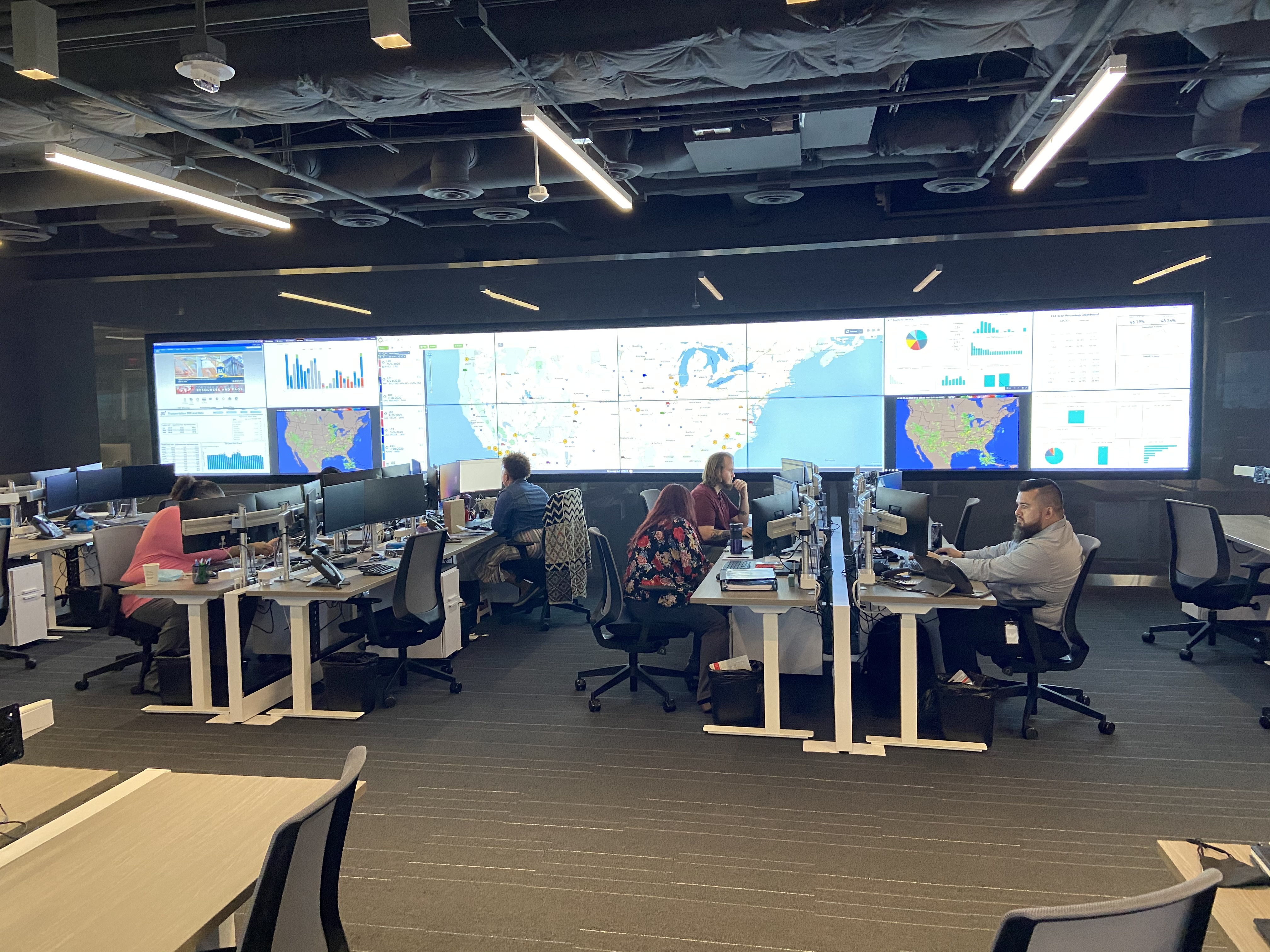 Inside an office, there are rows of employees sitting as desks looking at their computers. There are 16 tv screens at the front with various kinds of information on them