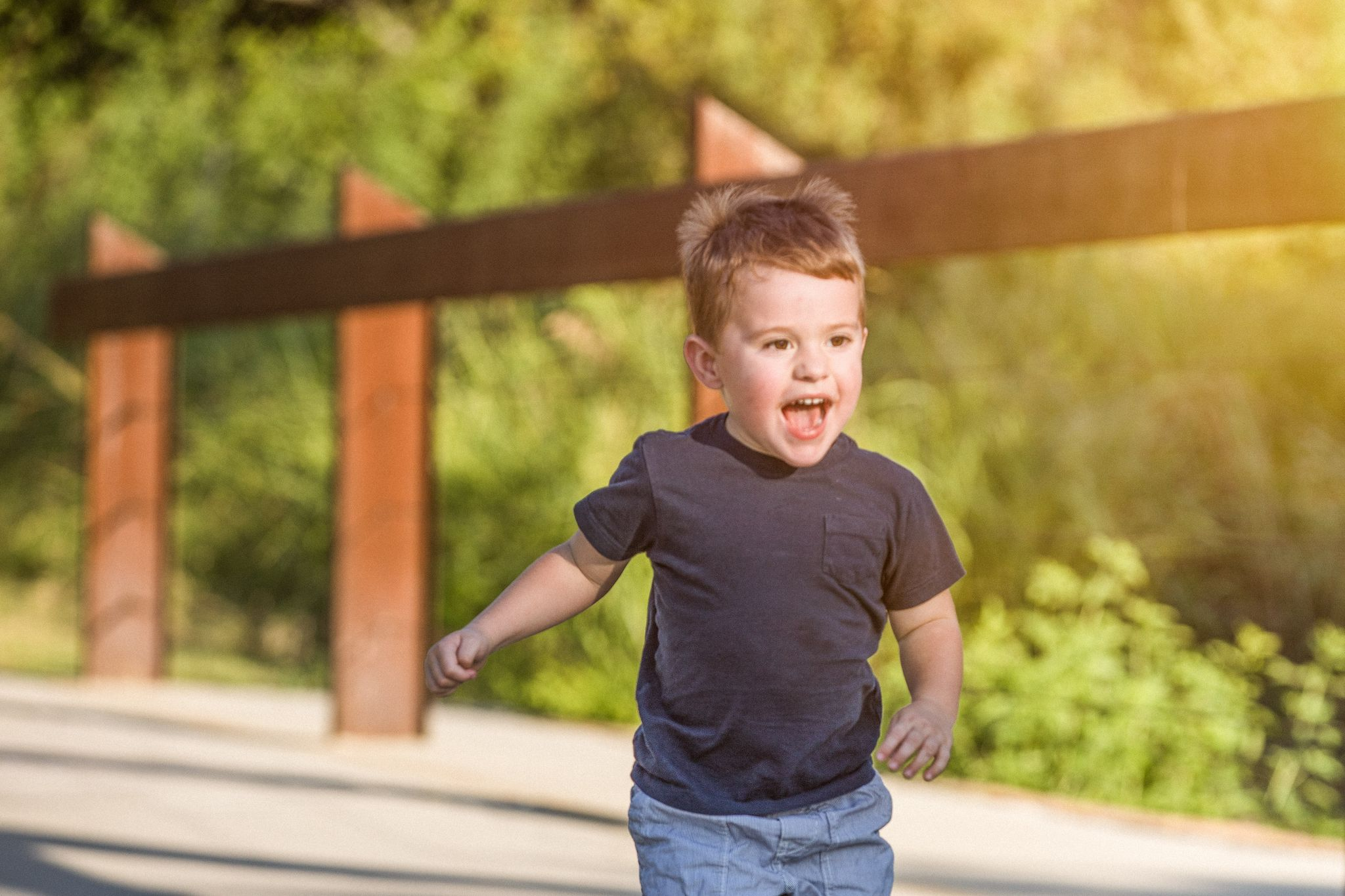 A young boy smiling and running.