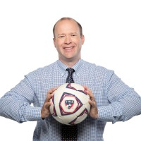 Dan Hunt smiles while holding an FC Dallas soccer ball.