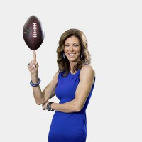 Charlotte Jones wears a bright blue dress and smiles while balancing a football on her pointer finger.